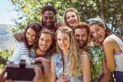 Jeunes amis heureux posant ensemble Photo stock