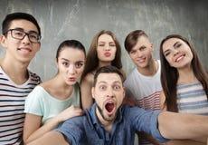 Jeunes amis heureux prenant le selfie Images stock