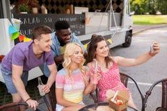 Jeunes amis heureux prenant le selfie au camion de nourriture Image stock