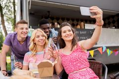 Jeunes amis heureux prenant le selfie au camion de nourriture Images stock