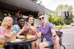 Jeunes amis heureux prenant le selfie au camion de nourriture Photos stock