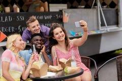 Jeunes amis heureux prenant le selfie au camion de nourriture Photo libre de droits