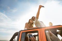 Jeunes amis heureux prenant le selfie pendant un voyage par la route Photographie stock libre de droits