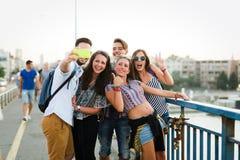 Jeunes amis heureux prenant le selfie sur la rue Image libre de droits