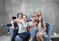 Jeunes amis heureux prenant le selfie tout en se reposant sur le sofa Photographie stock libre de droits