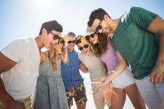 Jeunes amis heureux regardant dans le téléphone portable Image stock