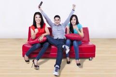 Jeunes amis heureux regardant la TV à la maison Photo libre de droits