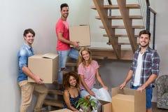 Jeunes amis heureux replaçant dans la nouvelle maison Images stock