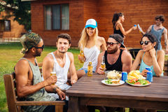 Jeunes amis heureux s'asseyant et parlant à la table dehors Image libre de droits