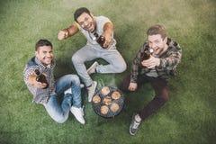 Jeunes amis heureux s'asseyant sur l'herbe et la bière potable tout en grillant la viande Image stock