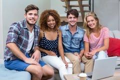 Jeunes amis heureux s'asseyant sur le sofa à la maison Photo libre de droits