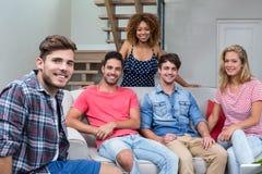 Jeunes amis heureux s'asseyant sur le sofa dans le salon Photographie stock libre de droits