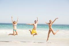 Jeunes amis heureux sautant sur la plage Photo stock