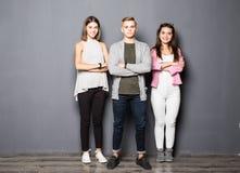 Jeunes amis heureux se tenant à l'intérieur sur le fond gris Image libre de droits