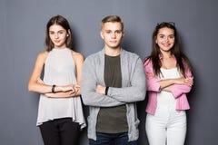 Jeunes amis heureux se tenant à l'intérieur sur le fond gris Image stock