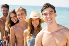 Jeunes amis heureux se tenant contre la mer Image stock