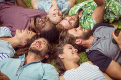 Jeunes amis heureux se trouvant sur l'herbe Images libres de droits