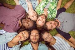 Jeunes amis heureux se trouvant sur l'herbe Photo libre de droits