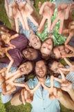 Jeunes amis heureux se trouvant sur l'herbe Photo stock