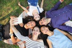 Jeunes amis heureux se trouvant sur l'herbe et prenant le selfie Photos stock