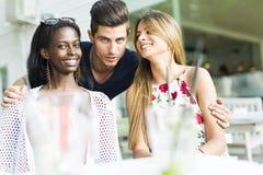 Jeunes amis heureux souriant dehors étant près de l'un l'autre Photographie stock