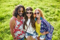 Jeunes amis hippies de sourire sur le champ vert Images stock