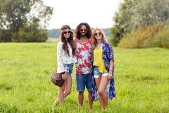 Jeunes amis hippies de sourire sur le champ vert Photos libres de droits