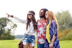 Jeunes amis hippies de sourire sur le champ vert Photographie stock