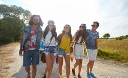 Jeunes amis hippies heureux de sourire à la voiture de monospace Photographie stock libre de droits