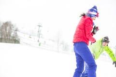 Jeunes amis jouant dans la neige Photo libre de droits