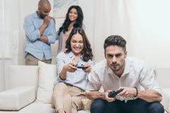 Jeunes amis jouant des jeux vidéo à la maison Photos stock