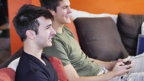 Jeunes amis jouant des jeux vidéo avec des manettes Photos libres de droits