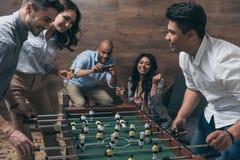 Jeunes amis jouant le football de table ensemble à l'intérieur Photo stock