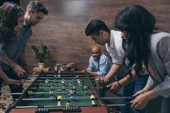 Jeunes amis jouant le football de table ensemble à l'intérieur Photos libres de droits