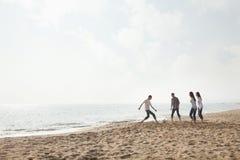 Jeunes amis jouant le football sur la plage Images libres de droits