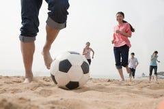 Jeunes amis jouant le football sur la plage Photos stock