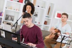 Jeunes amis jouant le piano et la signature de guitare Images libres de droits