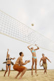 Jeunes amis jouant le volleyball sur la plage Image stock