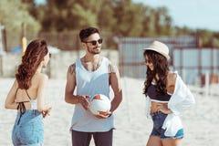 Jeunes amis jouant le volleyball sur la plage sablonneuse Image stock