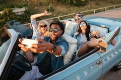 Jeunes amis joyeux prenant le selfie avec le téléphone portable dans le cabriolet Photo stock