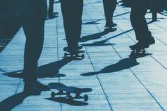 Jeunes amis jugeant des planches à roulettes dans des mains extérieures sur le parc de patin de ville - amis de l'adolescence aya Photographie stock libre de droits