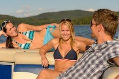 Amis les prenant un bain de soleil se trouvant sur le yacht d'été Images stock