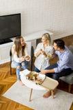 Jeunes amis mangeant de la pizza dans la chambre Photographie stock libre de droits