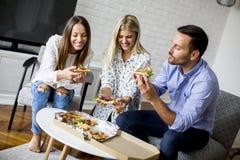 Jeunes amis mangeant de la pizza dans la chambre Images libres de droits