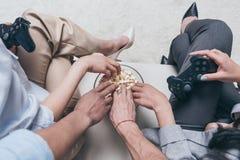 Jeunes amis mangeant du maïs éclaté tout en jouant des jeux vidéo à la maison Images stock
