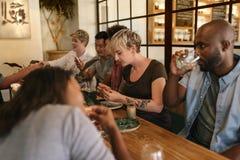 Jeunes amis mangeant et buvant ensemble à une table de Bistros Image stock