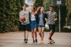 Jeunes amis marchant avec la planche à roulettes et le basket-ball Photos stock