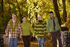 Jeunes amis marchant en stationnement d'automne Image libre de droits