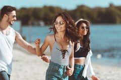 Jeunes amis marchant ensemble à la plage sablonneuse Images stock