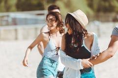 Jeunes amis marchant ensemble à la plage sablonneuse Photographie stock libre de droits
